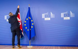 An EU official hangs the Union Jack next to the European Union flag at the VIP entrance at the European Commission headquarters in Brussels on Tuesday, Feb. 16, 2016. British Prime Minister David Cameron is visiting EU leaders two days ahead of a crucial EU summit. (AP Photo/Geert Vanden Wijngaert)