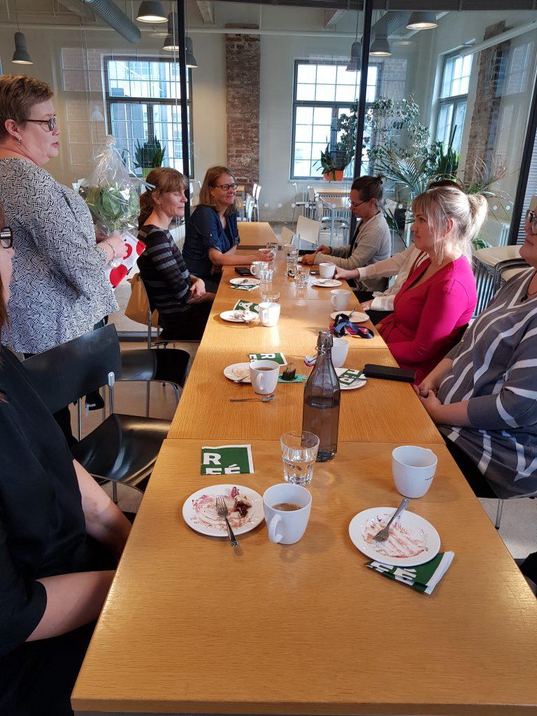 personer vid kaffebord blombukett.