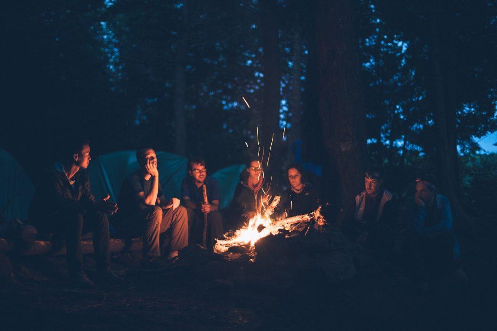 Ungdomar kring en lägereld.
