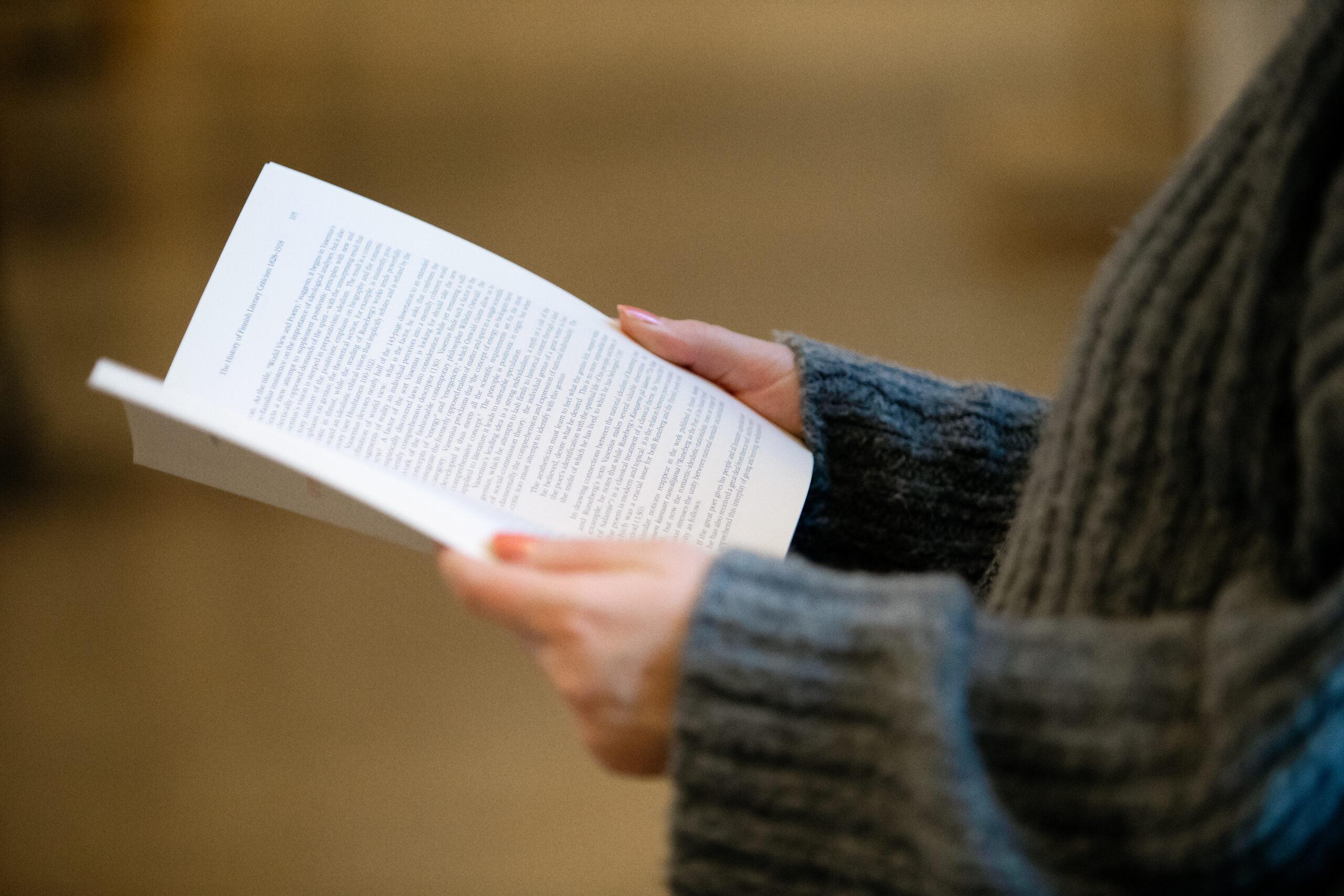 Person som håller i bok.